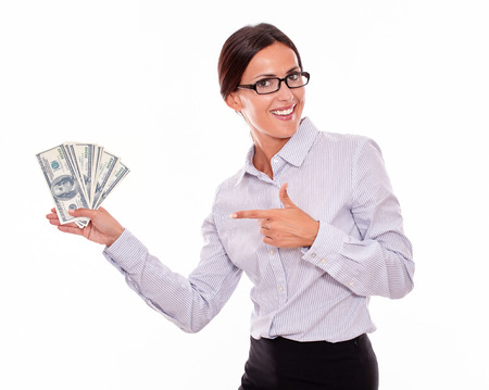 hair tied back: Impressed brunette businesswoman holding dollar bills with an excited gesture pointing at the money while smiling and looking at the camera wearing a button down shirt and her hair tied back, isolated Stock Photo