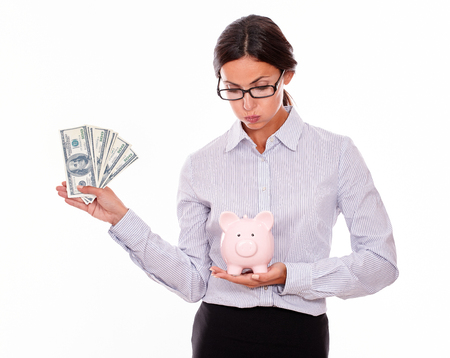 button down shirt: Businesswoman holding pink porcelain piggy bank in one hand and money with the other hand while looking satisfied at the piggy bank wearing her hair back in a button down shirt on a white background Stock Photo