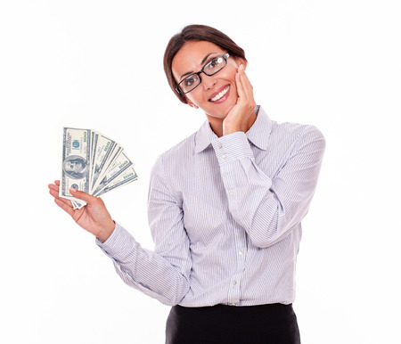 tied down: Happy smiling brunette businesswoman holding dollar bills while smilingly looking at the camera and marveling with one hand on her chin wearing a button down shirt and her hair tied back, isolated Stock Photo