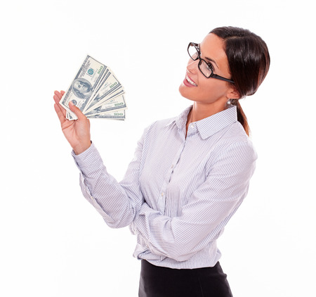 hair tied back: Pensive brunette businesswoman holding dollar bills and smiling while looking away, wondering and wearing a button down shirt with her hair tied back on a white background Stock Photo