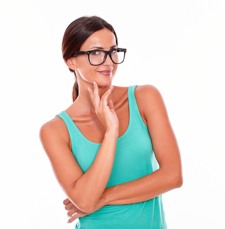 hair back: Contemplating brunette woman in green tank top looking at the camera with a reflective gesture of a hand on her chin while contemplating and wearing her long hair back on a white background Stock Photo