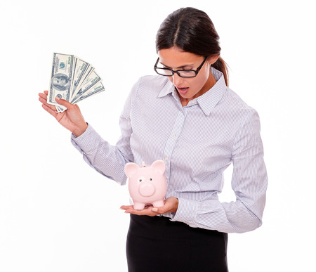 impressed: Impressed businesswoman holding pink porcelain piggy bank in one hand and money in the other hand while looking at the piggy bank and wearing her hair back on a white background Stock Photo
