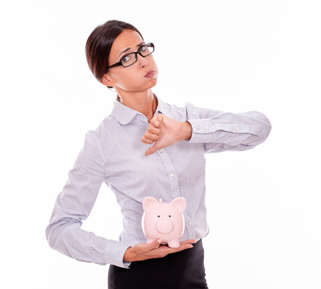 button down shirt: Businesswoman holding pink porcelain piggy bank with disapproval and a thumb down gesture wearing her hair back and a button down shirt while looking at camera on a white background Stock Photo