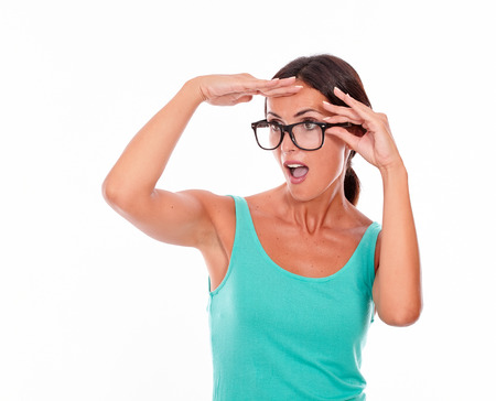 hair tied back: Shocked adult woman with a hand to her forehead touching her glasses with the other hand while looking into the distance wearing her long hair tied back in a green tank top on a white background