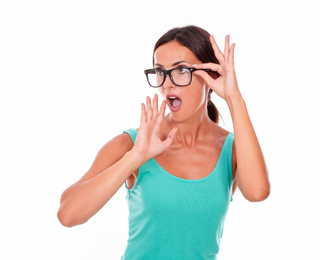 hair tied back: Shocked adult woman with a hand to her mouth while touching her glasses with the other wearing her long hair tied back in a green tank top on a white background Stock Photo