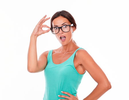 hair tied back: Shocked caucasian woman touching her glasses while looking at the camera with an open mouth and wearing her long hair tied back in a green tank top on a white background