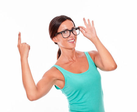 hair tied back: Adult woman pointing at copy space above her head while looking at the camera with a confident smile and wearing her long hair tied back in a green tank top touching her glasses on a white background Stock Photo