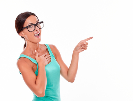 hair tied back: Surprised woman pointing at copy space next to her while looking at the camera with one hand on her chest and wearing her long hair tied back in a green tank top on a white background Stock Photo