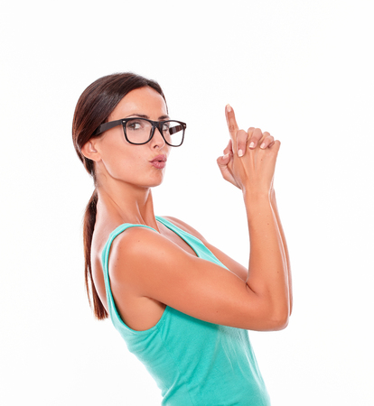 hair tied: Pouting woman pointing at copy space above her head with both hands while looking at the camera with a charismatic smile and wearing her long hair tied back in a green tank top on a white background