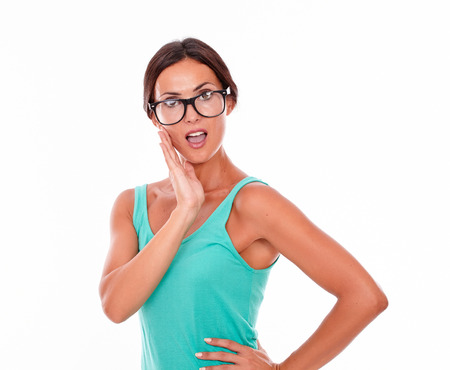 hair tied back: Surprised adult woman holding her chin while looking at the camera with an open mouth and wearing her long hair tied back in a green tank top on a white background