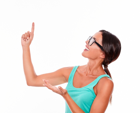 hair tied back: Adult woman pointing at copy space above her head while looking at it with a confident smile and wearing her long hair tied back in a green tank top and glasses on a white background Stock Photo