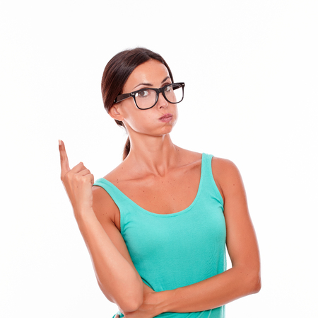 Stressed woman pointing at copy space above her head with one hand while looking at the camera wearing her long hair tied back in a green tank top on a white background