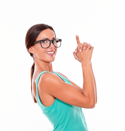 hair tied back: Adult woman pointing at copy space above her head with both hands while looking at the camera with a charismatic smile and wearing her long hair tied back in a green tank top on a white background Stock Photo