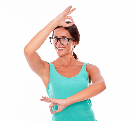 hair tied back: Satisfied adult woman smiling at camera while dancing and showing an ok sign with both hands wearing her long hair tied back in a green tank top on a white background Stock Photo