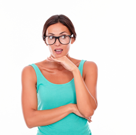 lack of confidence: Mistaken caucasian woman with her hand to mouth while looking away as if she made a mistake wearing her long hair tied back in a green tank top on a white background