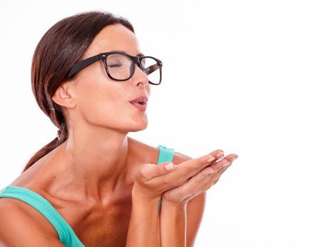 Adult caucasian woman blowing a kiss with her eyes closed while wishing and gesturing with her hands on a white background