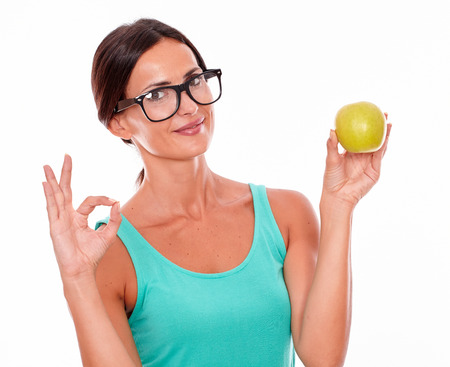 congratulating: Congratulating woman holding an apple looking at the camera while showing a perfect sign wearing a green tank top on a white background