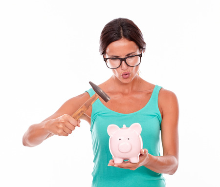 pouting: Pouting brunette woman holding pink piggy bank and a hammer while looking at the piggy bank with glasses and a green tank top isolated