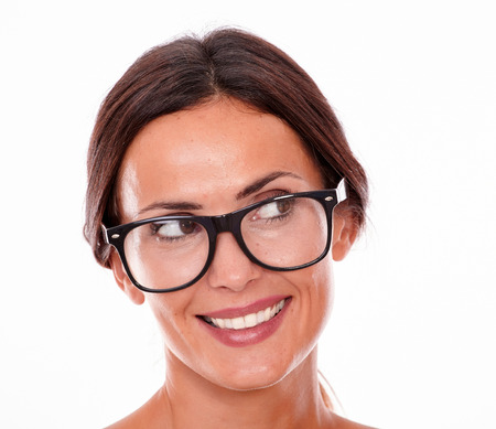 back straight: Attractive smiling brunette female with glasses looking away with a toothy smile and wearing her straight hair tied back on a white background