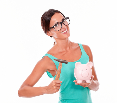 toothy smile: Smiling woman with pink piggy bank and a hammer while looking at the camera with a toothy smile wearing glasses and a tank top, isolated