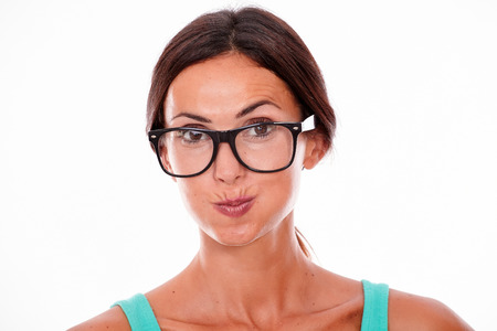 hair back: Attractive pouting brunette female with glasses looking at the camera while wearing her hair back and a green t-shirt on a white background