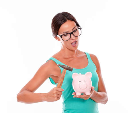 mouthed: Thinking woman with pink piggy bank and a hammer while looking at the piggy bank open mouthed with glasses and a green tank top, isolated Stock Photo