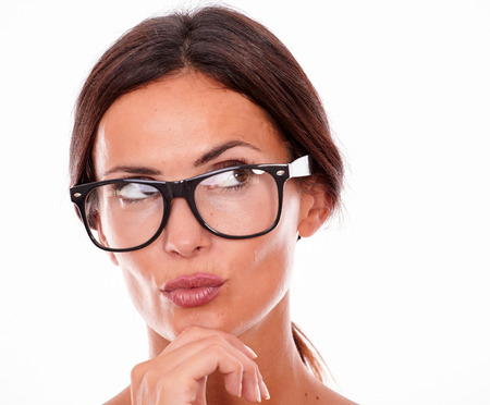 Attractive pouting brunette female holding her hand to her chin while looking away with glasses on a white background Stock Photo