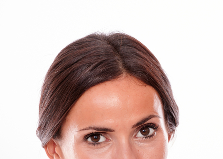 hair tied back: Caucasian brunette woman looking at camera with brown eyes from the nose up section of her face and her hair tied back, isolated