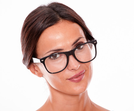 secretive: Attractive wondering brunette female with glasses looking at the camera with a secretive smile and wearing her straight hair back on a white background Stock Photo