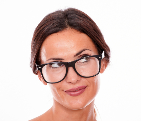 hair tied: Attractive smiling brunette female with glasses looking away with a thoughtful smile and her straight hair tied back on a white background Stock Photo
