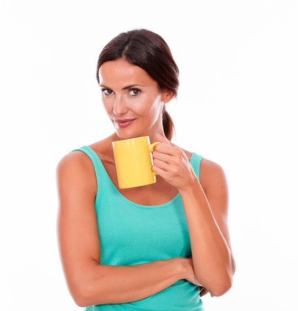 secretive: Secretive smiling brunette with a coffee mug looking at camera while wearing a green tank top and her hair tied back on white background