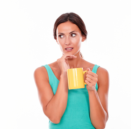 hair tied back: Worried brunette with a coffee mug looking away with her hand to chin, wearing a green tank top and her hair tied back isolated Stock Photo