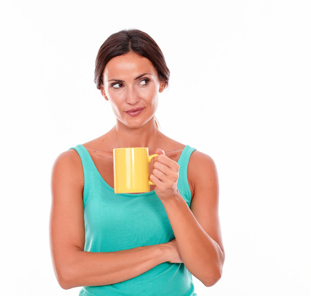 hair tied back: Thinking brunette woman with a coffee mug looking away while wearing a green tank top and her hair tied back on white background