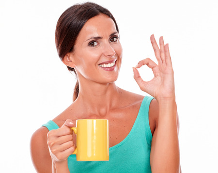 perfect sign: Smiling brunette woman with coffee mug looking at camera gesturing a perfect sign while wearing a green tank top on isolated background