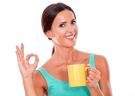 perfect sign: Celebrating brunette woman with coffee mug looking at camera gesturing a perfect sign wearing a green tank top and her long hair tied back isolated