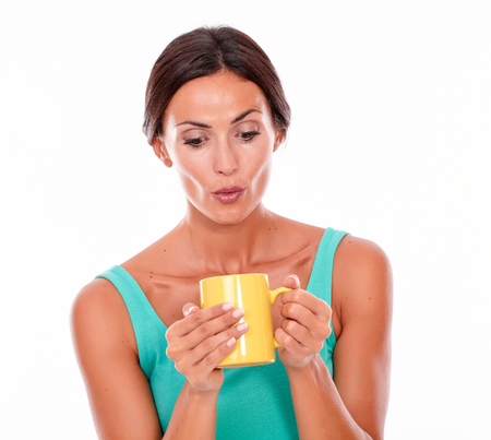 pouting: Pouting brunette woman with coffee mug looking at her coffee while wearing a green tank top and her long hair tied back on white background Stock Photo