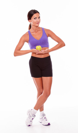hair tied back: Healthy brunette holding apple with both hands looking at camera legs crossed while wearing violet and black gymnastic clothing and her hair tied back isolated