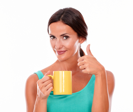 hair tied back: Happy brunette woman with coffee mug looking at camera gesturing thumbs up and wearing a green tank top and her long hair tied back isolated