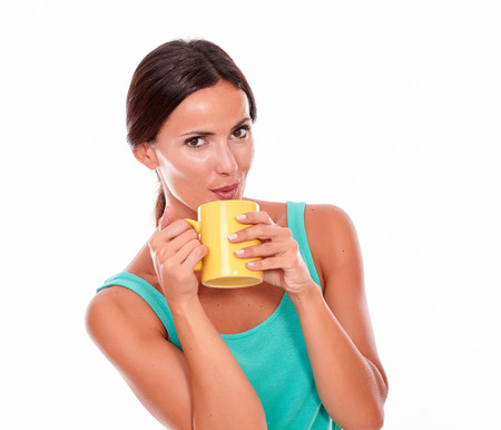 hair tied: Pouting brunette holding a coffee mug with both hands, looking at camera while wearing a green tank top and her hair tied back, isolated