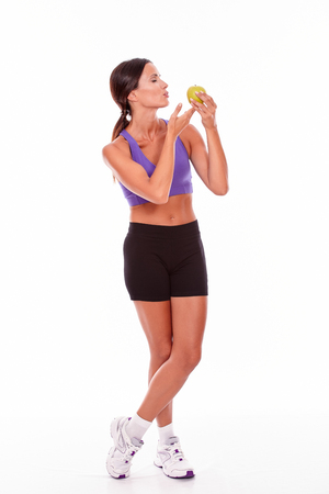 legs crossed: Healthy smiling brunette with an apple looking at apple and legs crossed, wearing violet and black gymnastic clothing with her hair tied back isolated