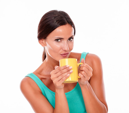 hair tied back: Pouting brunette woman with coffee mug looking at camera secretively while wearing a green tank top and her long hair tied back on white background