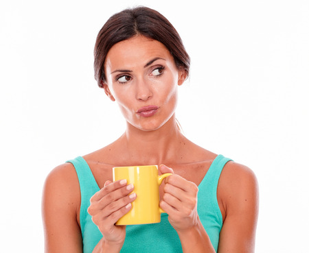 hair tied back: Pouting brunette woman holding coffee mug with both hands while looking at camera wearing a green tank top and her long hair tied back isolated Stock Photo