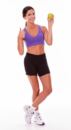 hair tied back: Healthy smiling brunette with an apple looking at camera gesturing thumbs up wearing violet and black gymnastic clothing with her hair tied back isolated Stock Photo