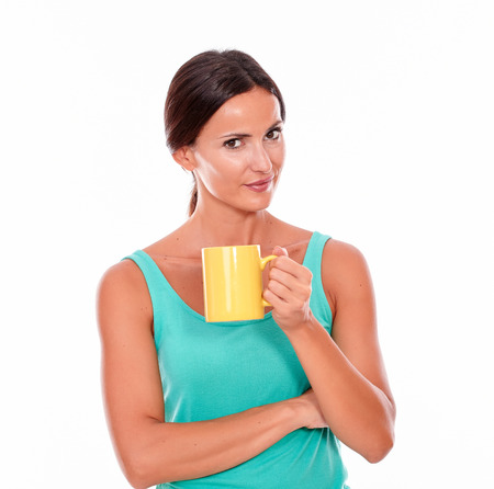 tied hair: Thinking brunette woman with a coffee mug looking at camera while wearing a green tank top and her long hair tied back on white background