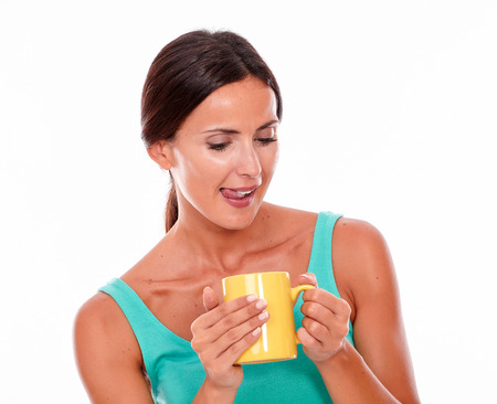 licking in isolated: Satisfied brunette woman with coffee mug looking at coffee, licking her lips while wearing a green tank top and her long hair tied back isolated