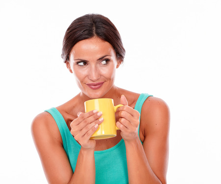 hair tied back: Smiling brunette woman with coffee mug looking away secretively while wearing a green tank top and her long hair tied back on white background Stock Photo
