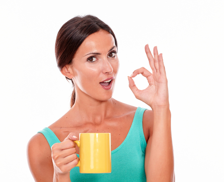 hair tied back: Celebrating brunette woman with coffee mug looking at camera gesturing a perfect sign wearing a green tank top and her long hair tied back isolated