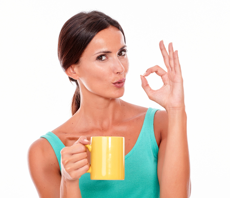 perfect sign: Pouting brunette woman with coffee mug looking at camera gesturing a perfect sign wearing a green tank top and her long hair tied back isolated Stock Photo