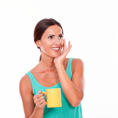hair tied back: Smiling brunette with a coffee mug looking away with her hand to face wearing a green tank top and her hair tied back, isolated Stock Photo