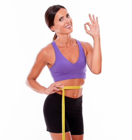 perfect sign: Beautiful smiling brunette gesturing a perfect sign, looking at camera, while measuring her waist wearing violet and black gymnastic clothing isolated